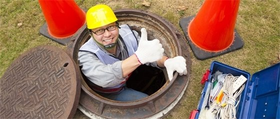 Wastewater worker emerging from manhole next to toolbox
