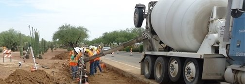 photo depicting road workers pouring cement at roadside