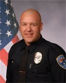 Photo of Officer Robert Mohr in uniform blues with United States flag and gray backdrop