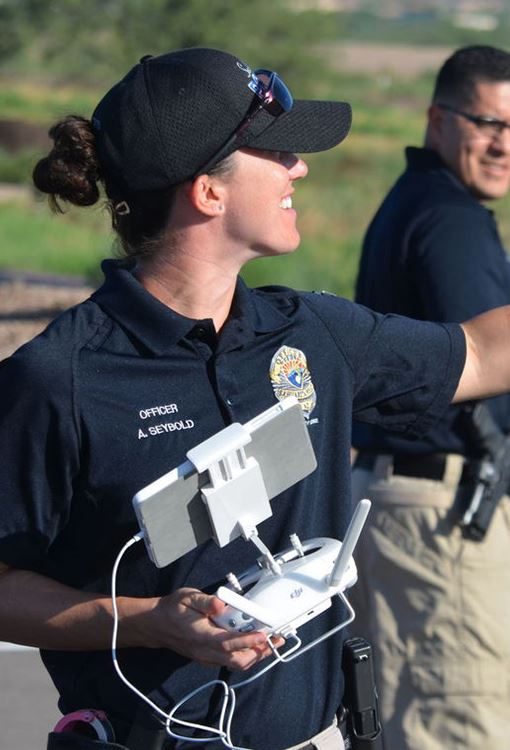 Police woman holding remote control for a drone