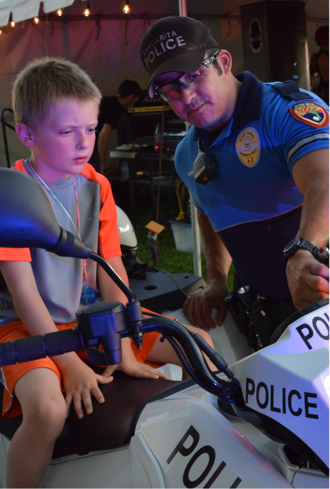 Photo of SPD officer showing a young boy the siren and lights atop his SPD ATV.