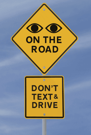 "road sign reading ""eyes on the road; don't text and drive"""