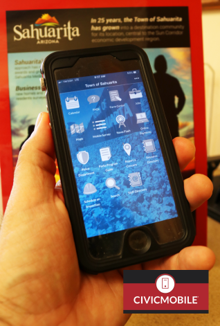 Photograph of cell phone in hand with Sahuarita advertisement in background