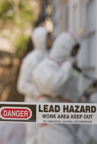 LEAD HAZARD CAUTION TAPE IN FRONT OF WORKERS REMOVING LEAD