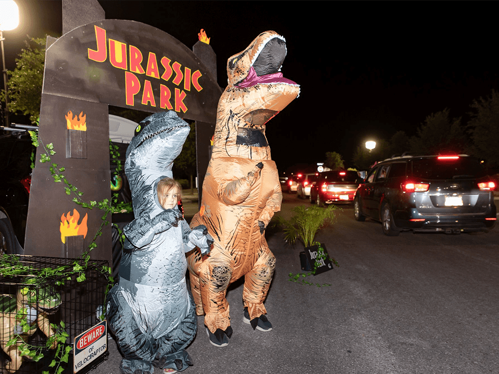 A child and adult dressed in inflatable t-rex costumes in front of a Jurassic Park themed display