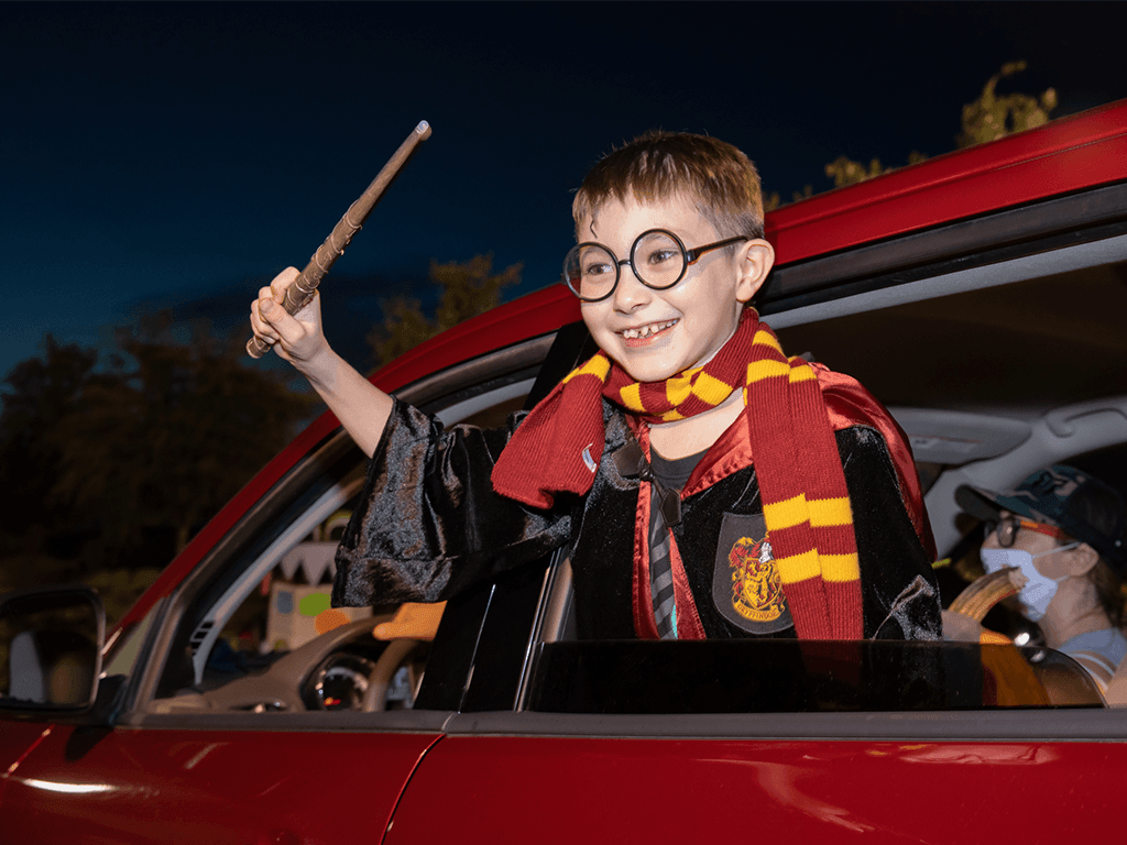 Boy dressed as Harry Potter with wand, scarf, and glasses, out car window smiling